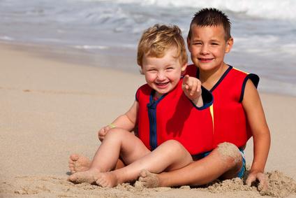 Kinder mit Rettungsweste am Strand